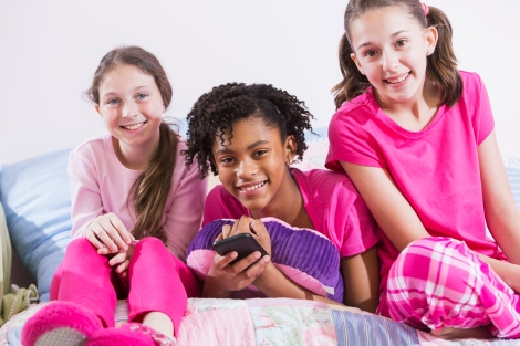 A group of three multiracial preteen girls having a sleepover.  They are wearing pink pajamas, sitting side by side on a bed.  The African American girl in the middle, lying on her stomach hugging a pillow, is holding a mobile phone.